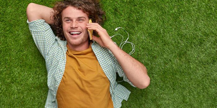 pocitovka muž se válí na trávě a telefonuje