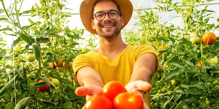 mladý muž má radost z rajčat